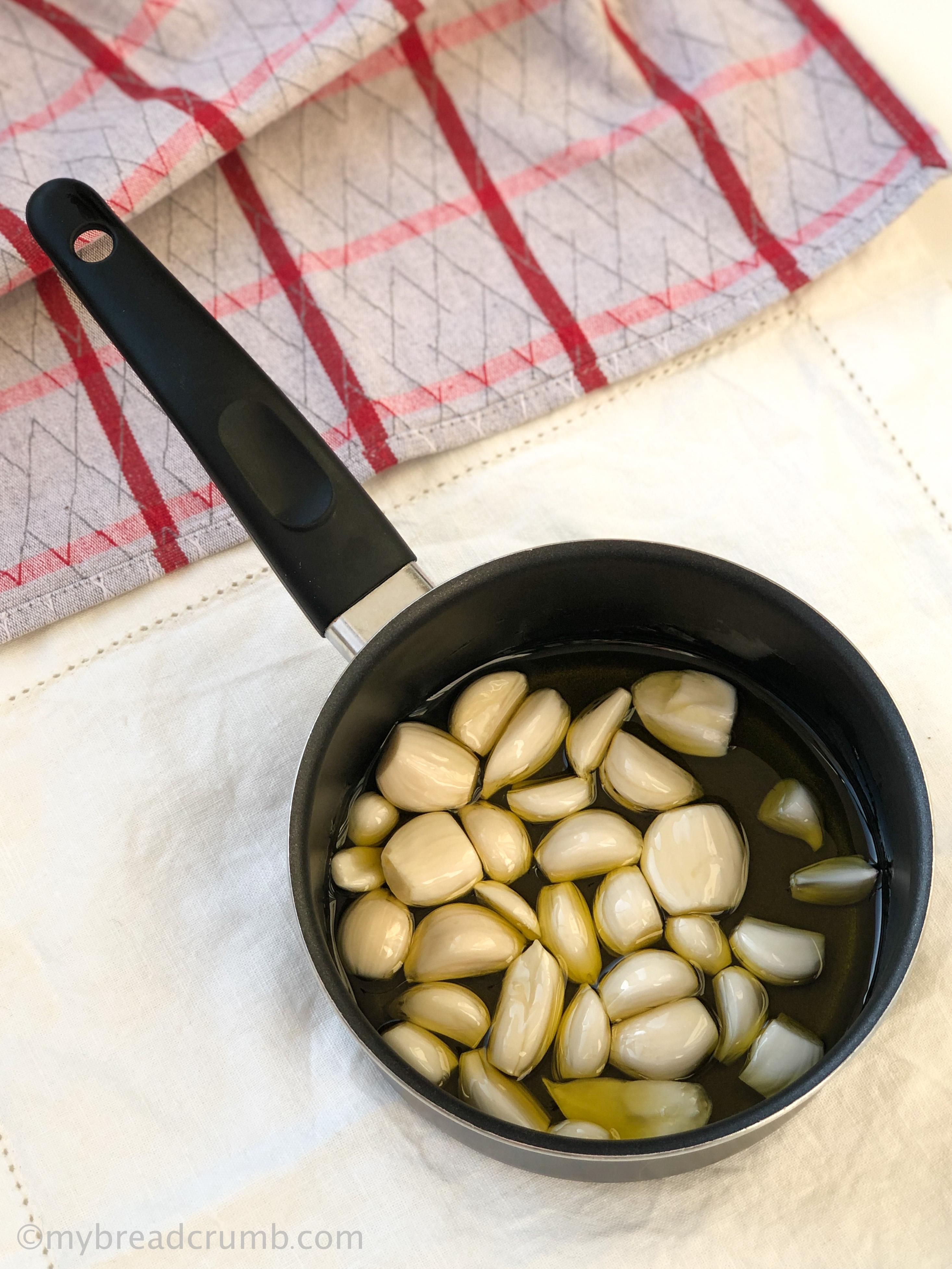Черный сотейник с дольками чеснока в оливковом масле, готовые к приготовлению конфи