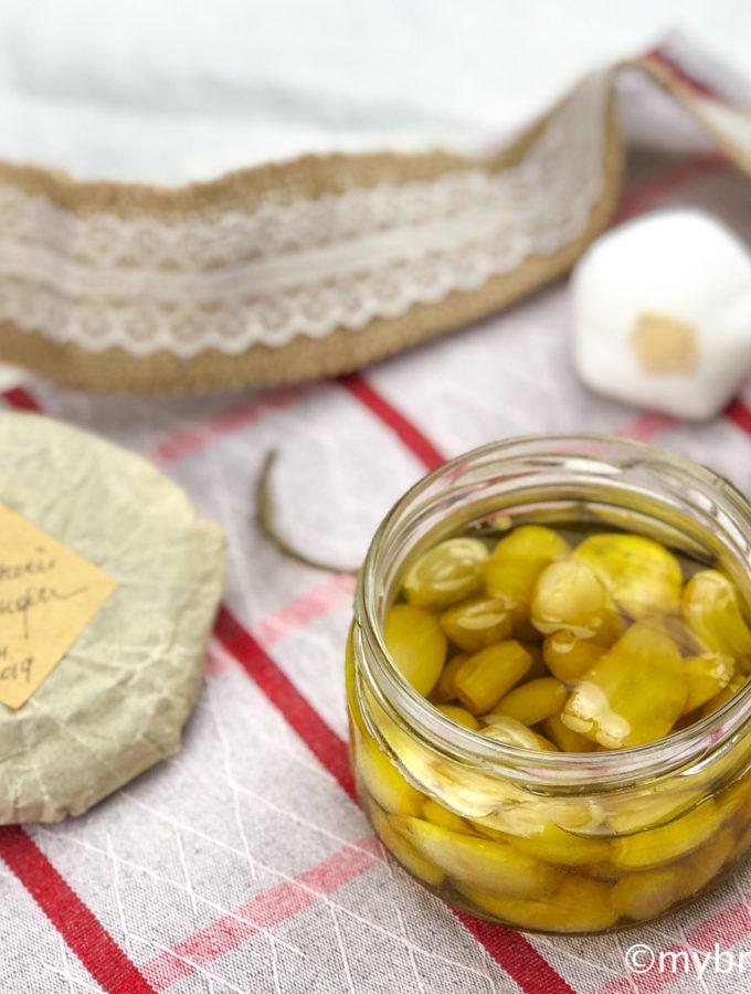 Открытая баночка чесночного конфи - томленого в оливковом масле чеснока