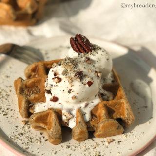 Бельгийская вафля на белой тарелке с шариком мороженого и посыпкой из ореха пекан