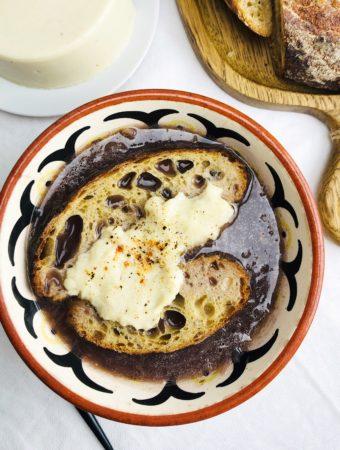 Луковый суп с кусочками хлеба и растительной моцареллой. На фоне белой скатерти и деревянной доски.