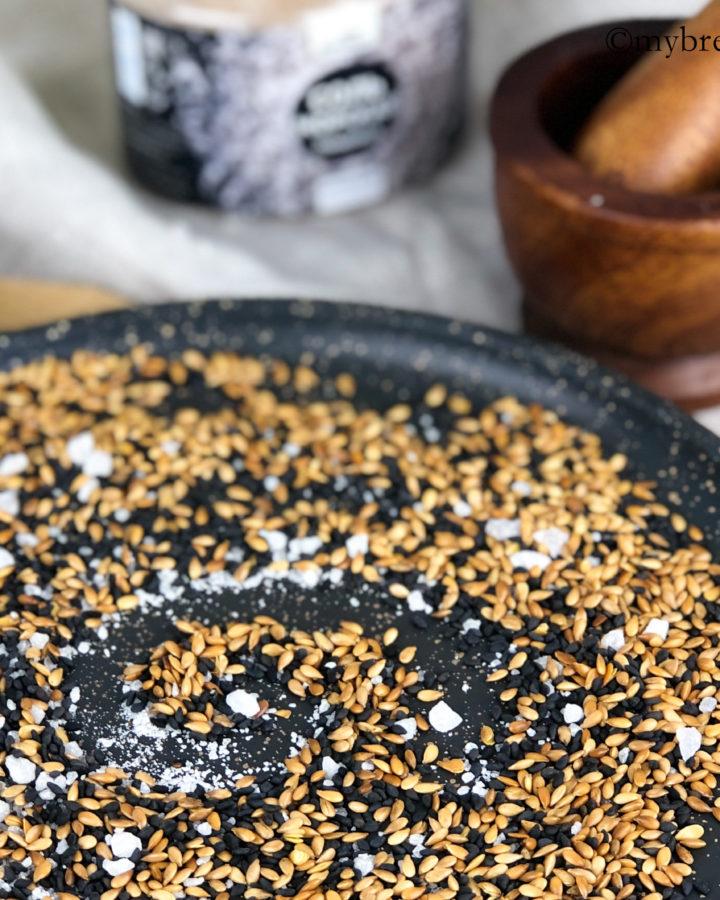 кунжут с морской солью на сковороде, на заднем плане - деревянная ступа